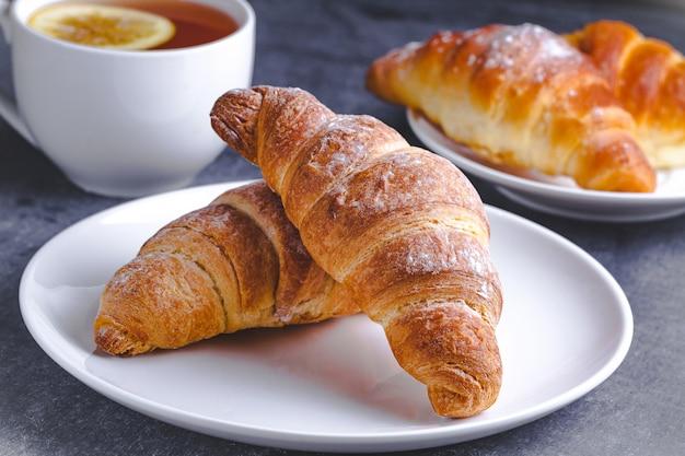 Versgebakken croissants en een kop warme thee met citroen voor traditioneel frans ontbijt op een donkere achtergrond