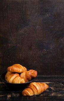Versgebakken croissants in een zwarte keramische plaat op de donkere houten achtergrond.