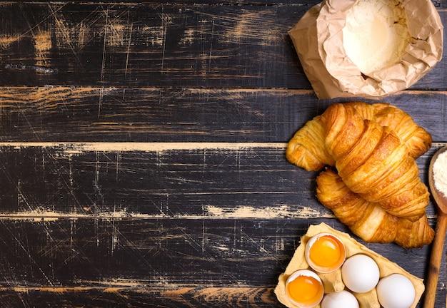 Versgebakken croissants met bloem, houten lepel, eieren en eidooiers