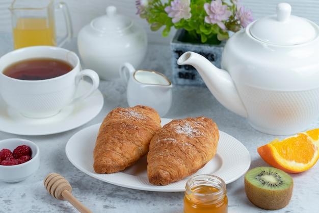Versgebakken croissants met een kopje thee en zoet fruit.