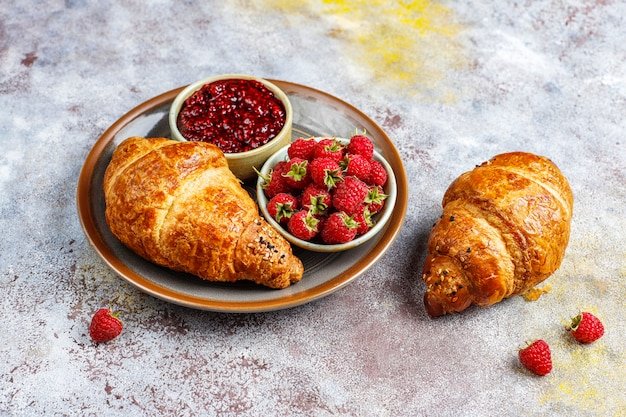 Versgebakken croissants met frambozenjam en frambozenfruit.