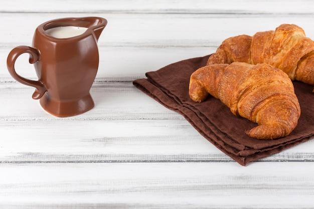 Versgebakken croissants op bruin servet, room in keramische melkkann op witte oude houten achtergrond. vers gebak voor het ontbijt. heerlijk dessert. close-up fotografie. horizontale banner.