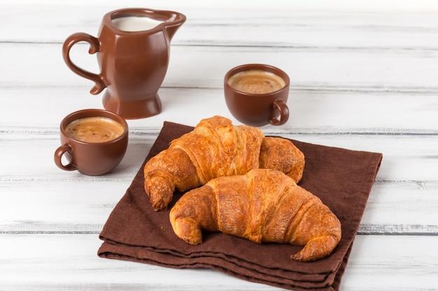 Versgebakken croissants op bruin servet, room, kopjes koffie in keramische gerechten op witte houten achtergrond. vers gebak voor het ontbijt. heerlijk dessert. close-up fotografie. horizontale banner