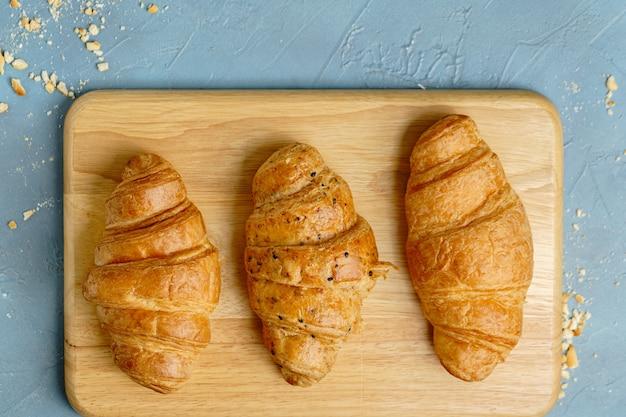 Versgebakken croissants op houten plaat, bovenaanzicht.
