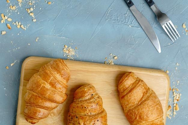 Versgebakken croissants op houten plaat.