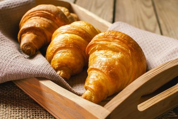 Versgebakken croissants op houten snijplank, bovenaanzicht. huisgemaakt of bakkerij.