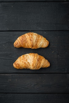 Versgebakken croissants set, op zwarte houten tafel achtergrond, bovenaanzicht plat lag
