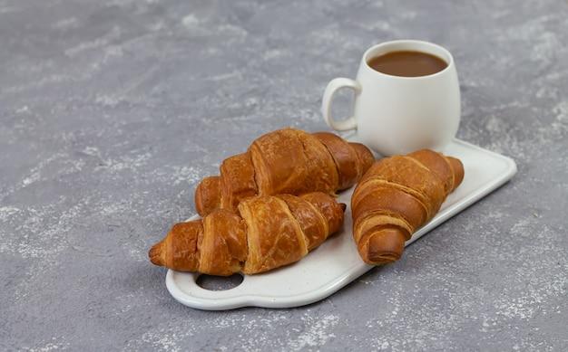 Versgebakken franse croissants en kopje koffie op rustieke stenen tafel