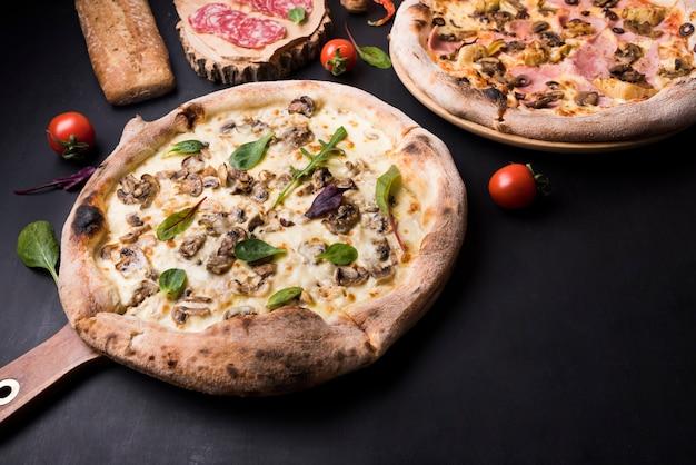 Versgebakken italiaanse pizza; pepperoni en cherry tomaat over zwart oppervlak