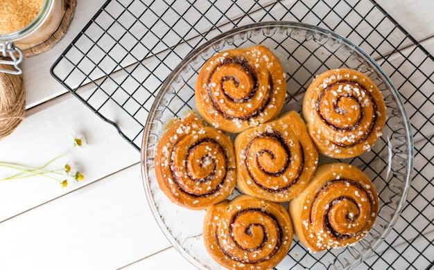 Versgebakken kaneelbroodjes met kruiden op een houten ondergrond. kanelbule - zweeds dessert. voedselconcept. bovenaanzicht, plat gelegd