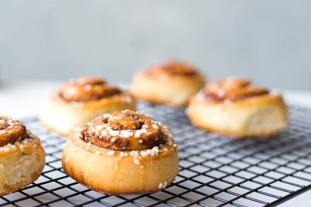 Versgebakken kaneelbroodjes met kruiden op een houten ondergrond. kanelbule - zweeds dessert. voedselconcept. rustieke stijl