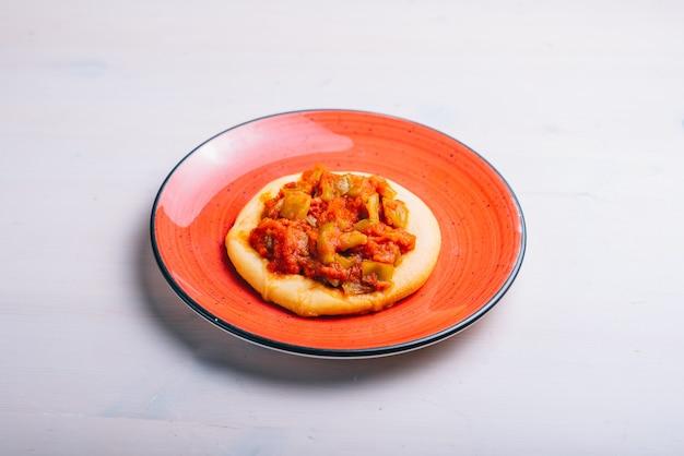 Versgebakken minipizza met tomaten en groenten. traditioneel spaans gebak met groenten.