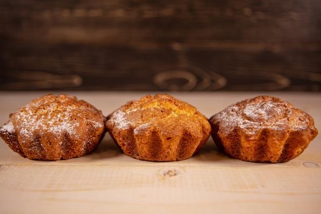 Versgebakken muffins muffins in poedersuiker op een houten achtergrond.