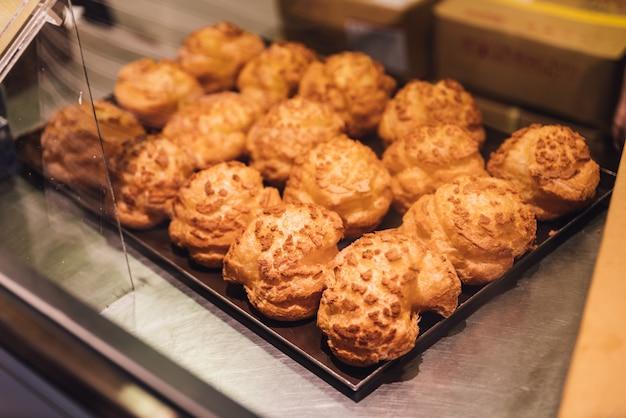 Versgebakken vanilla choux cream puffs voor verkoop.