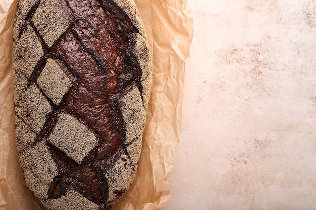 Versgebakken zelfgebakken brood op ambachtelijke zuurdesem rogge op oude lichte brawn steen of betonnen ondergrond. bovenaanzicht. voedsel koken achtergrond. ruimte kopiëren.
