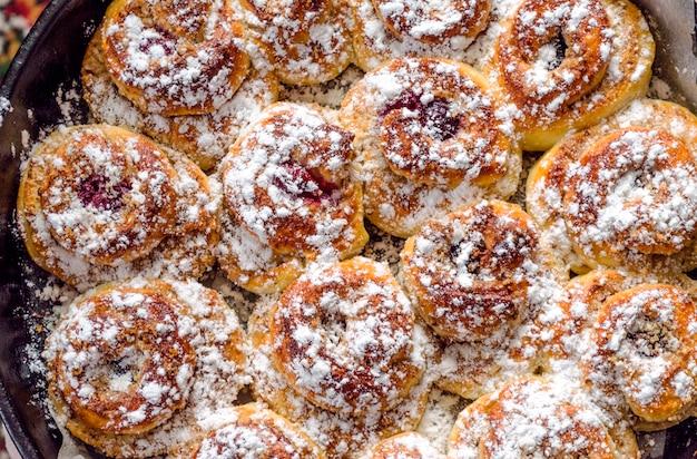 Versgebakken zelfgemaakte taarten in een bakplaat. kersenbroodjes in poedersuiker