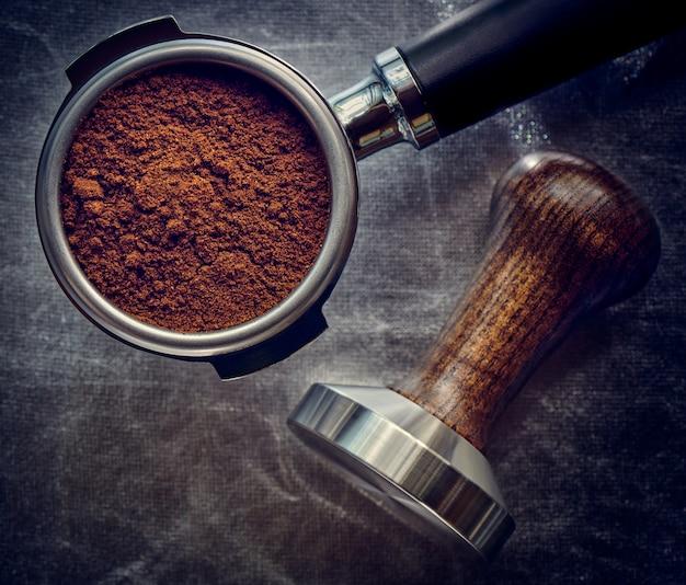 Versgemalen koffie in een koffiehoorn en temperament
