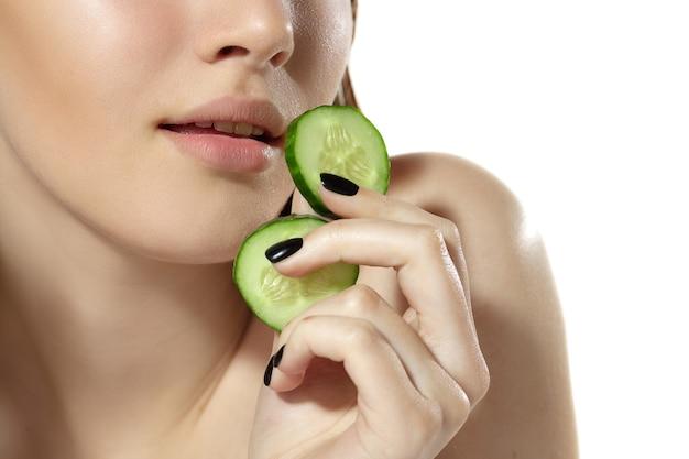 Versheid. close up van mooie jonge vrouw met verse plakjes komkommer op witte achtergrond. concept van cosmetica, make-up, natuurlijke en eco-behandeling, huidverzorging. glanzende en gezonde huid, gezondheidszorg.