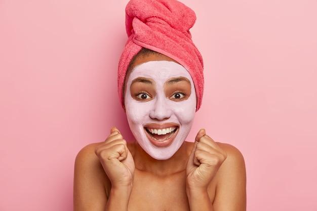 Versheid, douche, zelfzorgconcept. dolblij etnische dame heft gebalde vuisten, lacht positief, maakt schoonheidsbehandelingen na bad, gezicht bedekt met klei vochtinbrengend masker, naakt gezond lichaam
