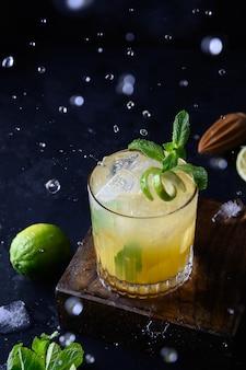 Versheid tropische limonade met limoen, sinaasappel en munt op zwart.