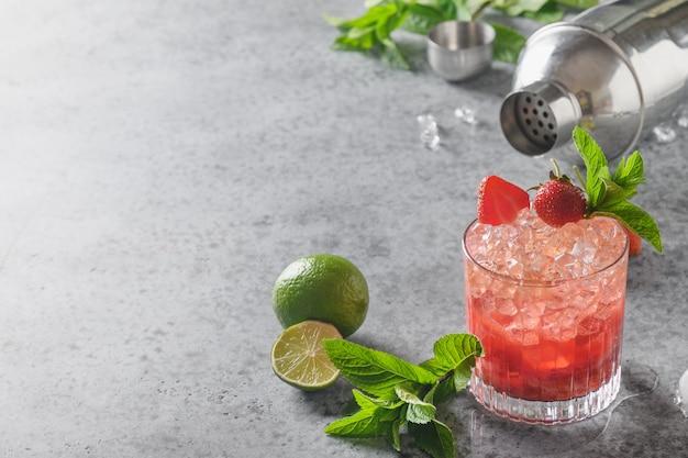 Versheidscocktail met aardbeienpuree, frisdrank, limonade, ijsblokje en limoen.