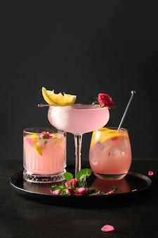 Versheidscocktails met roze gin en citroen op zwarte achtergrond verfrissende limonade voor feestelijk