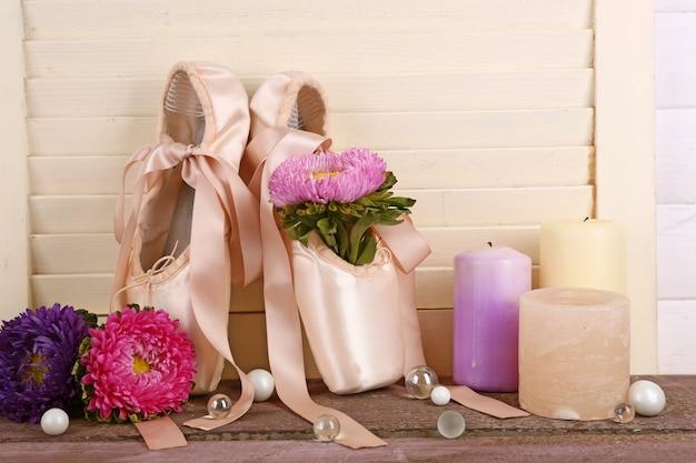 Versierd met bloemen en kaarsen balletschoenen op romige houten tafel