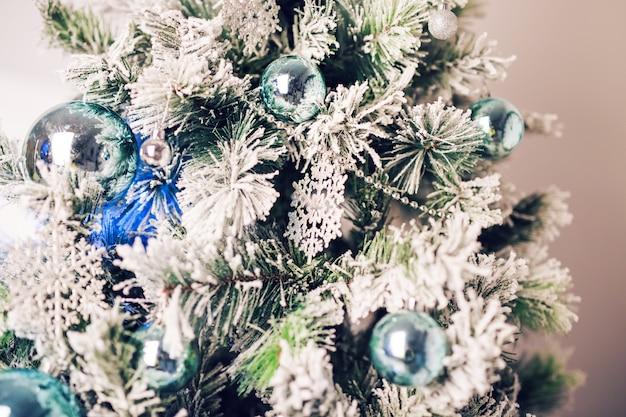 Versierde dennenboom en geschenkdozen in de woonkamer.