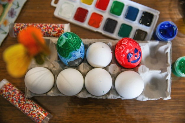 Versierde en witte eieren in een ambachtelijke standaard, verf en hagelslag op tafel
