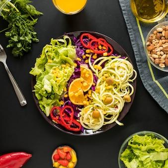 Versierde gezonde salade in plaat met dryfruits die op zwarte achtergrond wordt geschikt