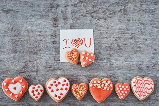 Versierde hartvormige koekjes en vel papier