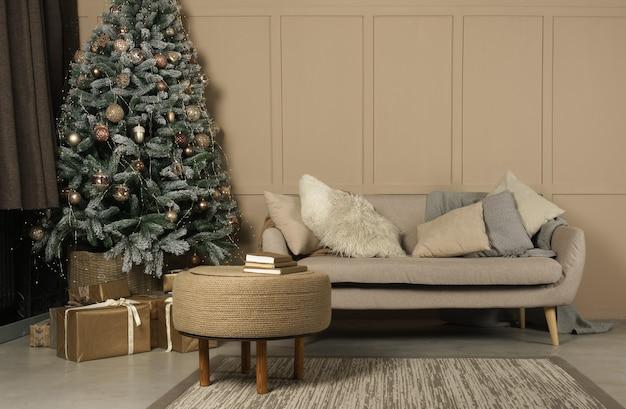Versierde kerstboom en geschenken in beige woonkamer