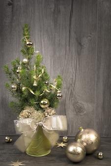 Versierde kerstboom en gouden kerstballen op hout,
