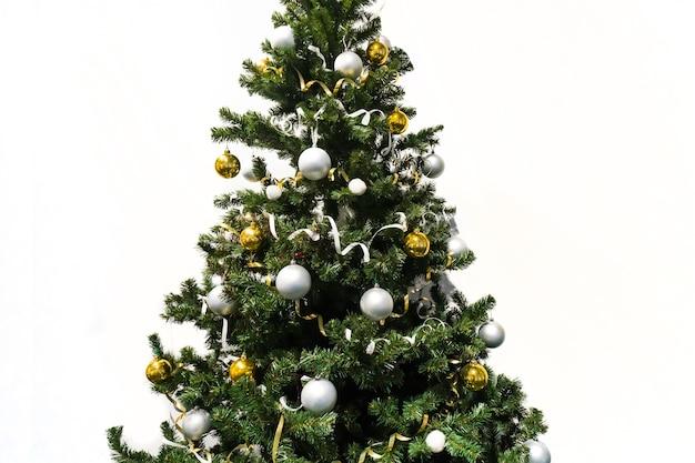 Versierde kerstboom geïsoleerd op een witte achtergrond. kerstboom versierd met gele en witte ballen en klatergoud.