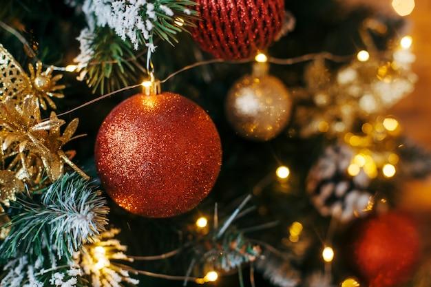 Versierde kerstboomclose-up. rode en gouden ballen en verlichte slinger met zaklampen.