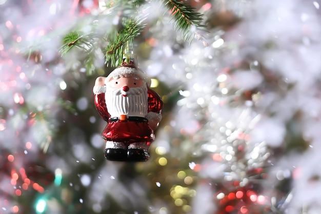 Versierde kerstboomtak met speelgoed in sneeuwval.