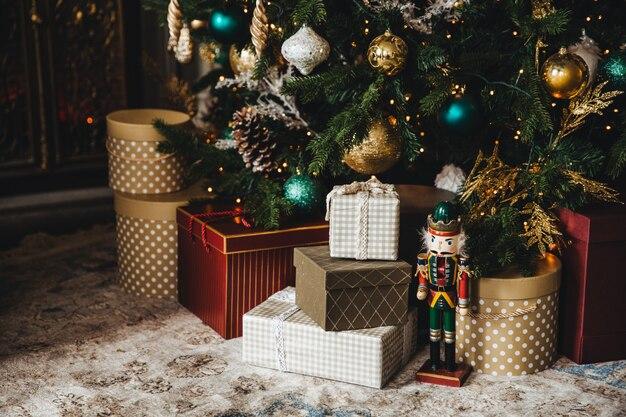 Versierde nieuwjaarsboom en veel cadeaus eronder. kerstboom met vele kleurrijke decoraties