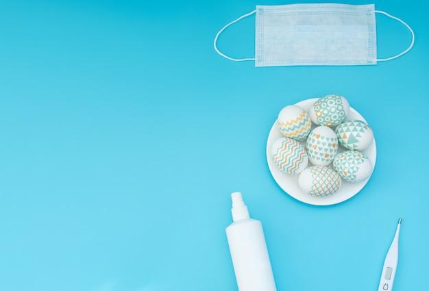 Versierde paaseieren liggen op de plaat, medisch gezichtsmasker, thermometer en ontsmettingsmiddel op blauw Premium Foto
