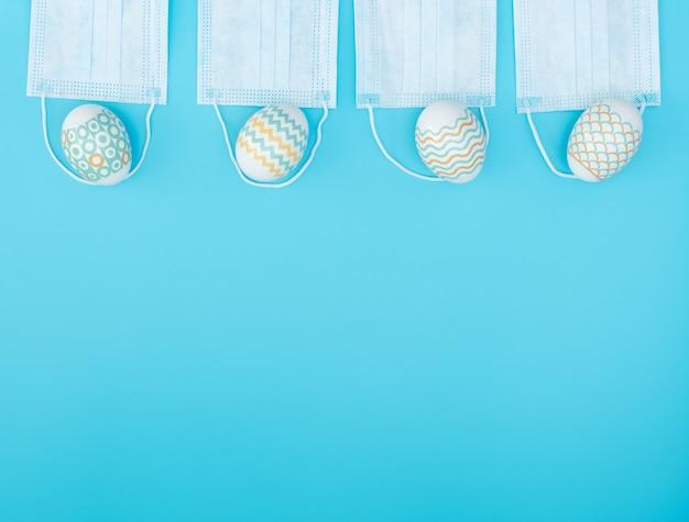Versierde paaseieren liggen op het medische gezichtsmasker op blauw