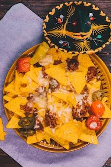 Versierde smakelijke mexicaanse nachos in plaat met mexicaanse hoed op tafel