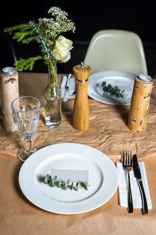 Versierde tafel klaar voor het diner. prachtig gedecoreerde tafel met bloemen, kaarsen, borden en servetten voor bruiloft of een ander evenement in het restaurant.
