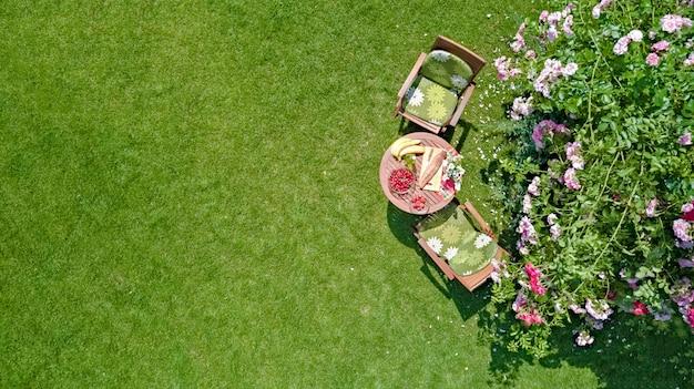 Versierde tafel met brood, aardbei en fruit in mooie zomerse rozentuin, luchtfoto bovenaanzicht van romantische datum tafel eten setting voor twee van bovenaf