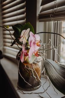 Versierde vaas met bloemen naast een raam