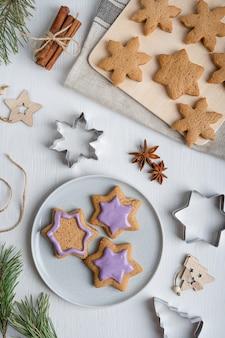 Versieren van zoete hartige peperkoekkoekjes met violet suikerglazuur op witte houten tafel met cutters