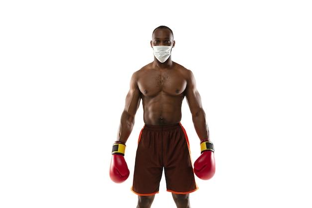 Versla het virus. afro-amerikaanse bokser met beschermend masker, handschoenen. nog steeds actief tijdens quarantaine. gezondheidszorg, geneeskunde, sportconcept.