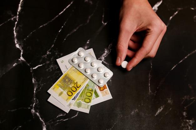 Verslaafde hand met geld om een dosis cocaïne, heroïne of een andere drug te kopen bij een drugsdealer.