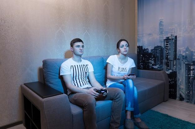 Verslaafde jonge man die een videogame speelt terwijl zijn vriendin thuis toezicht houdt op het proces op de bank voor een tv in een ontspannen sfeer
