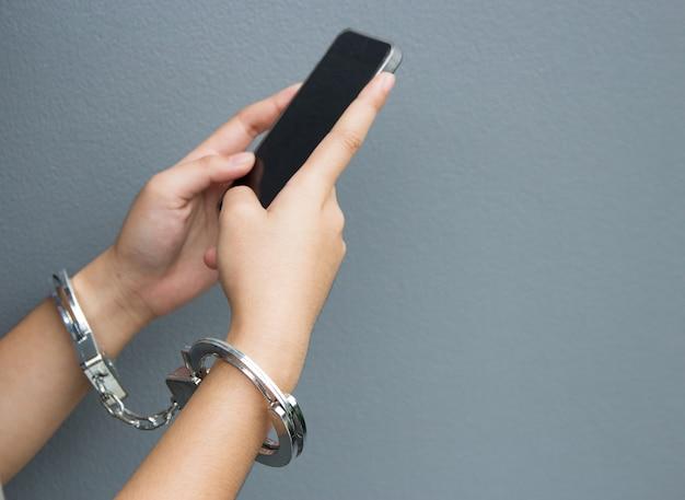 Verslaafde mobiele telefoon concept met hand en armband