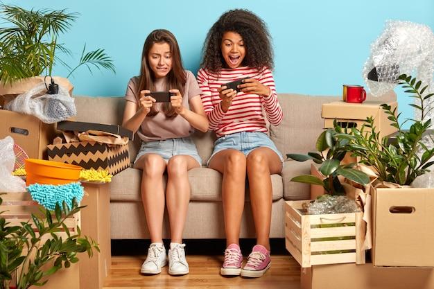 Verslaafde vriendinnen zittend op de bank met telefoons omringd door dozen
