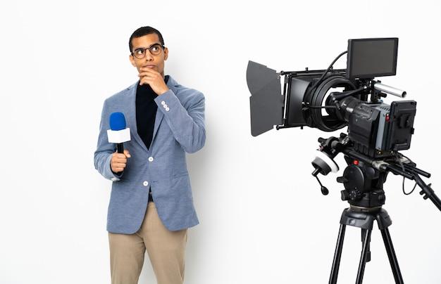 Verslaggever afrikaans-amerikaanse mens die een microfoon houden en nieuws over geïsoleerde witte muur rapporteren die twijfels en met verwarde gezichtsuitdrukking hebben